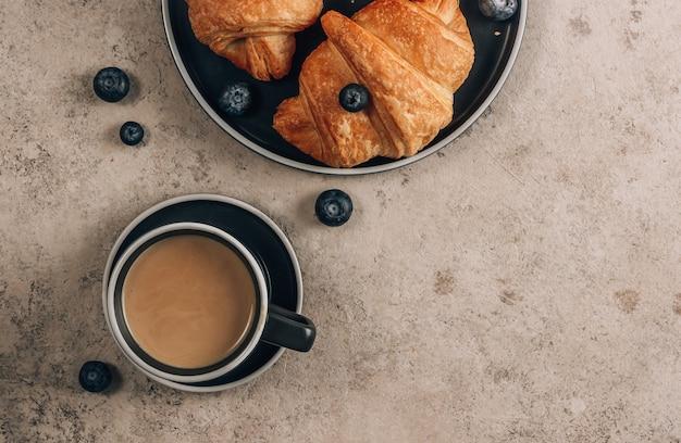Una tazza di caffè con croissant