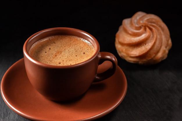 Tazza di caffè con eclairs su uno sfondo di pietra. vista dall'alto con copia spazio per il testo