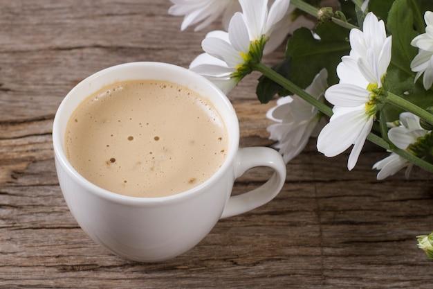 Tazza di caffè con schiuma su uno sfondo di legno con un bouquet di grandi margherite