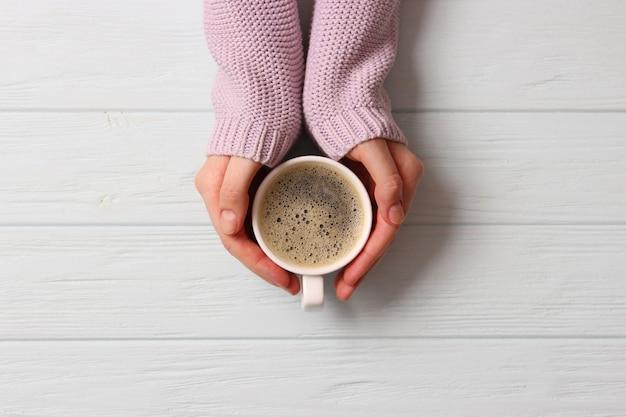 Tazza di caffè con schiumoso in mani femminili sul tavolo di legno. vista dall'alto. foto di alta qualità