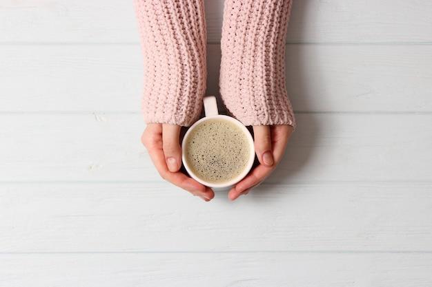 Tazza di caffè con schiumoso in mani femminili sulla vista del piano del tavolo in legno