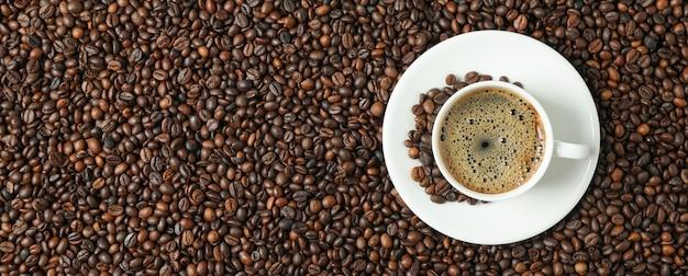 Tazza di caffè con schiuma schiumosa sul fondo dei fagioli