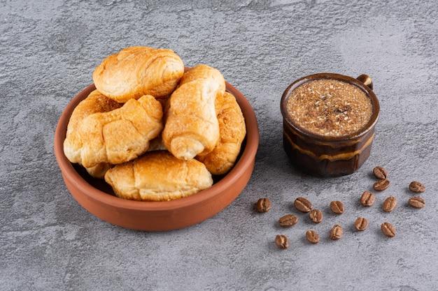 Tazza di caffè con croissant fatti in casa in una ciotola su grigio. Foto Premium