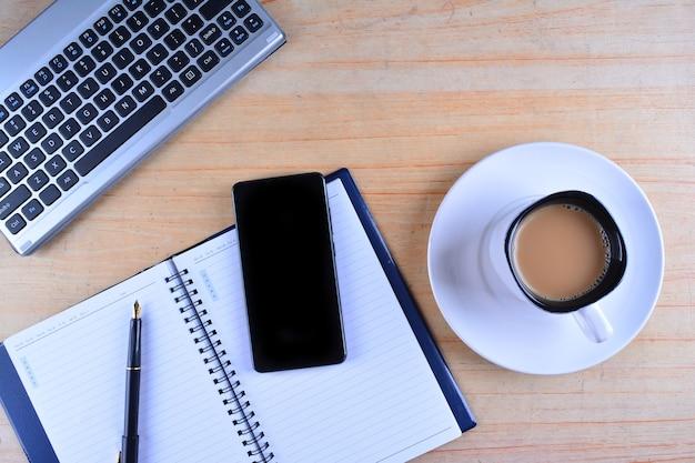 Tazza di caffè con tastiera e mouse, penna stilografica, notebook, calcolatrice e smartphone su un tavolo