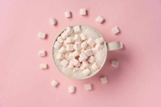 Una tazza di caffè con marshmallow sul muro rosa marshmallow giacciono intorno a forma di orologio