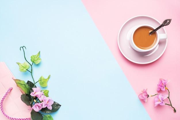 Una tazza di caffè con latte e ramo con fiori e foglie su uno sfondo pastello rosa con spazio di copia. disteso.