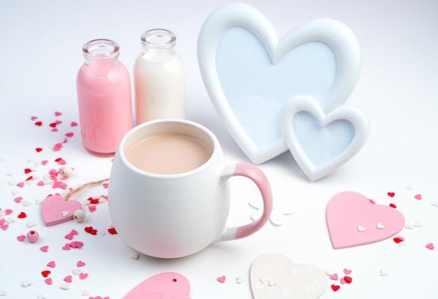 Una tazza di caffè con latte, una cornice a forma di cuori e una bottiglia di latte su uno sfondo bianco