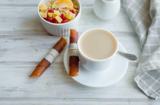 Tazza di caffè con latte, muesli per colazione con frutta, chips di frutta e pastiglia