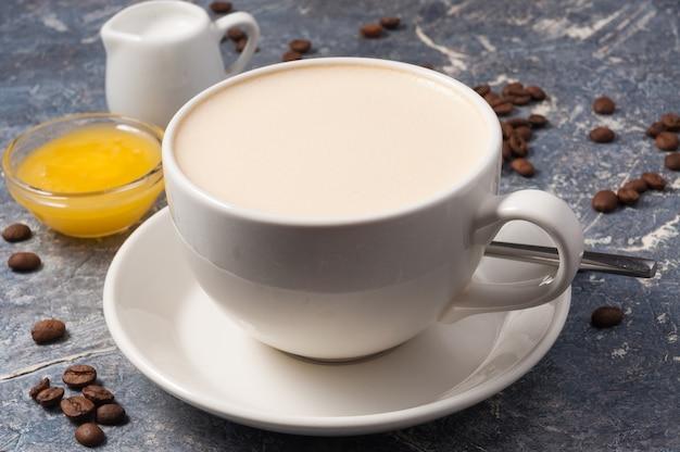 Tazza di caffè con latte e miele su uno sfondo grigio con chicchi di caffè