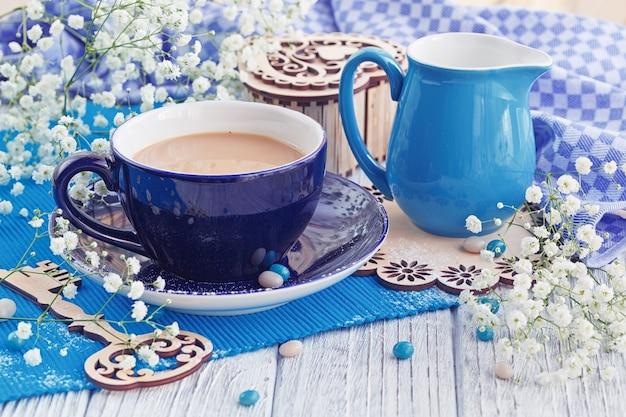 Tazza di caffè con latte è decorata da un tovagliolo blu, chiave di legno e piccoli fiori bianchi (gypsophila) su un tavolo di legno bianco