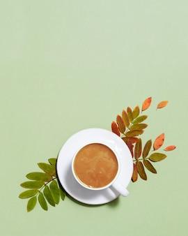 Tazza di caffè con latte e foglie autunnali gialle rosse su carta verde pastello