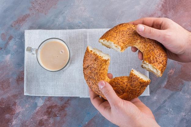 Una tazza di caffè con latte e bagel turco a fette sulla superficie di marmo