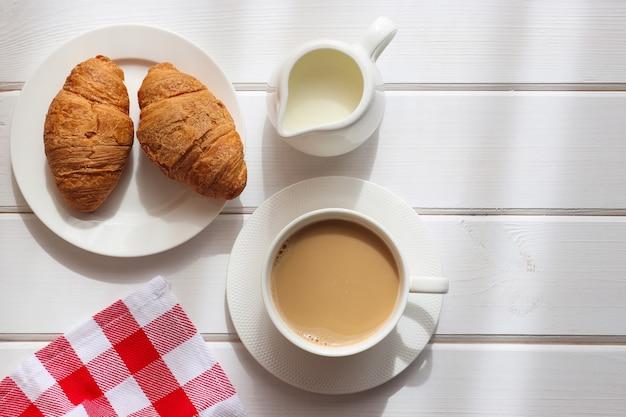 Tazza di caffè con latte e due croissant su un piatto su un tavolo di legno bianco con ombra leggera