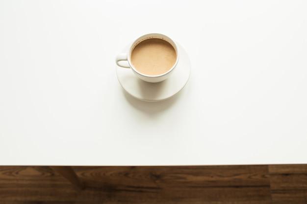 Tazza di caffè con latte sul tavolo bianco