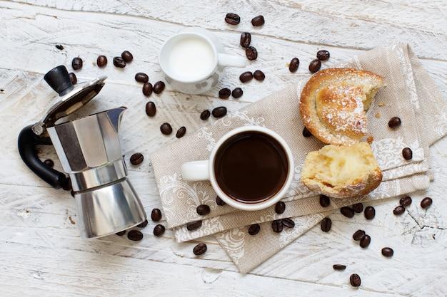 Tazza di caffè con pasticciotto su fondo rustico da vicino