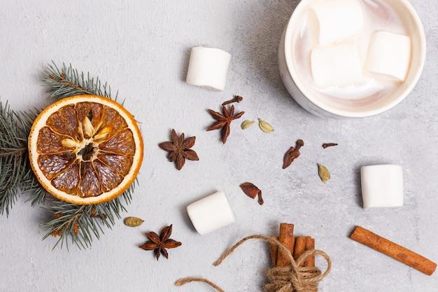 Una tazza di caffè con pezzi di marshmallow in cima e intorno circondati da bastoncini di cannella