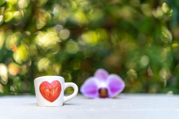 Tazza di caffè con cuore rosso stampato sulla sabbia su sfondo fiore soft focus.