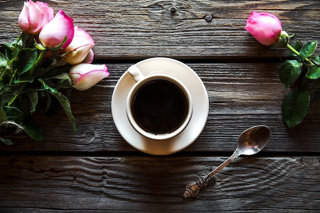 Tazza di caffè con rosa rossa ee copia spazio su uno sfondo di legno. colazione il giorno della mamma, la festa della donna, il giorno di san valentino o il giorno della nascita. bevanda calda, fiori