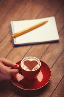 Tazza di caffè a forma di cuore e nota con penna su un tavolo di legno