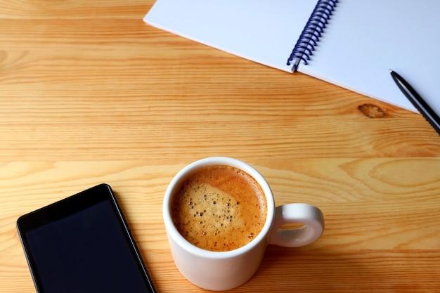 Tazza di caffè con smartphone e taccuino sulla tavola di legno per un concetto di telelavoro