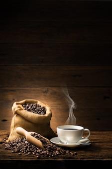 Tazza di caffè con fumo e chicchi di caffè su vecchio fondo di legno