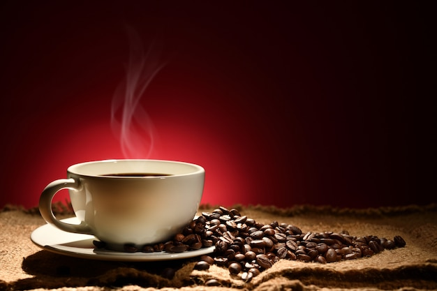 Tazza di caffè con fumo e chicchi di caffè su fondo marrone rossastro