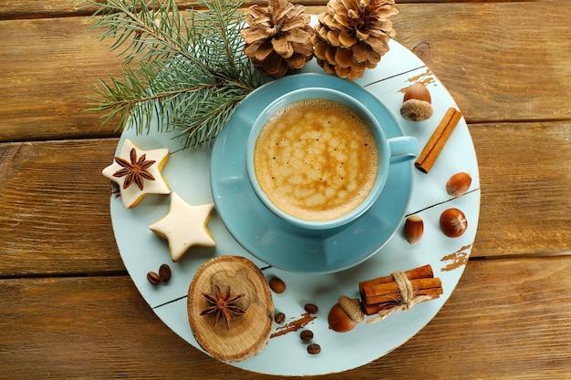 Tazza di caffè con biscotti a forma di stella e ramo di albero di natale su tappetino di legno