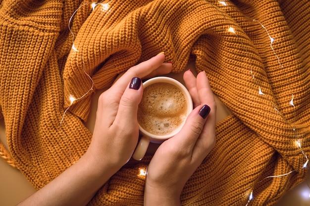 Tazza di caffè e con le mani della donna, maglione giallo.