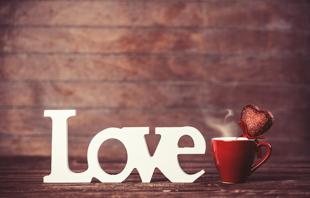 Tazza di caffè e parola amore sulla tavola di legno