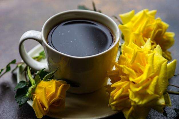 Tazza di caffè e rose gialle
