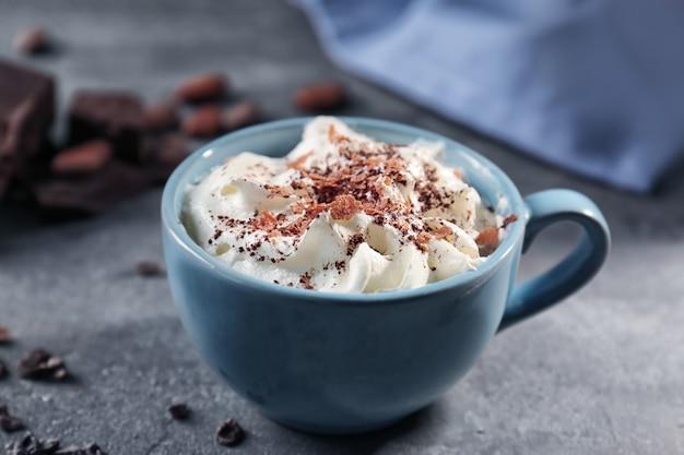 Tazza di deliziosa bevanda al cacao con panna montata sul tavolo della cucina del grunge