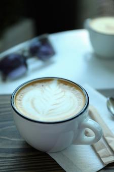 Tazza di caffè delizioso sulla tavola di legno all'aperto nel ristorante