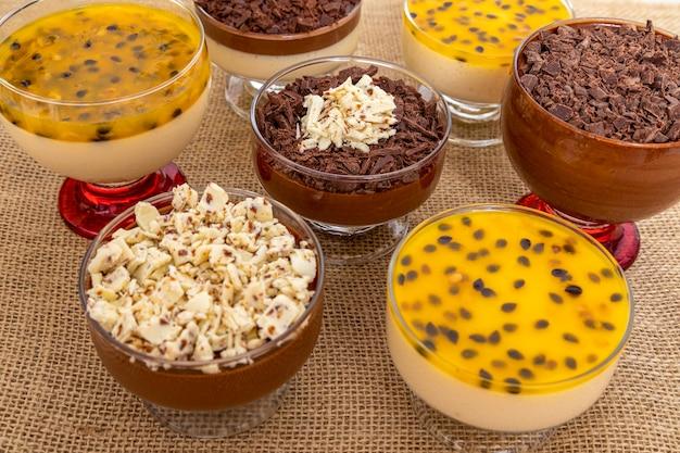 Coppa di dessert con mousse al cioccolato al latte e scaglie di cioccolato bianco, mousse alla ganache e mousse al frutto della passione.