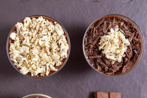 Coppa di dessert con mousse al cioccolato al latte con scaglie di cioccolato bianco