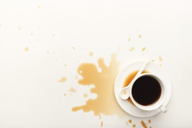Tazza di caffè espresso e caffè versato su sfondo bianco isolato, vista dall'alto. mockup per il design di pubblicità grunge, copia spazio
