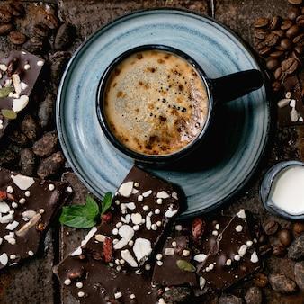 Tazza di caffè espresso con brocca di latte, cioccolato fondente fatto a mano, caffè e fave di cacao intorno su piastrelle di ceramica scure come sfondo. lay piatto, copia spazio. immagine quadrata