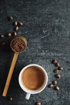 Tazza di caffè espresso e misurino con caffè macinato, vista dall'alto