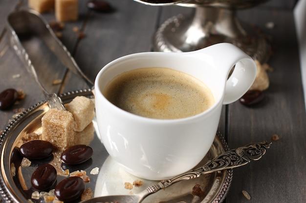 Tazza di caffè espresso, cubetti di zucchero e caramelle al cioccolato su fondo di legno rustico