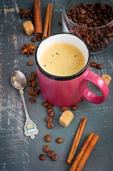 Tazza di caffè espresso con bastoncini di cannella e chicchi di caffè