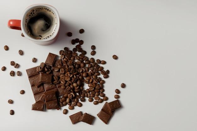 Tazza di caffè profumato, caffè in grani e cioccolato su sfondo bianco. copia spazio.
