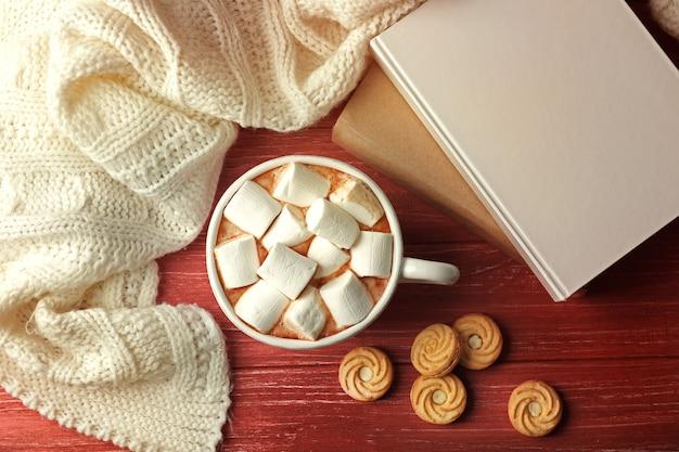 Tazza di caffè fresco con marshmallow e plaid a maglia su sfondo di legno, vista dall'alto