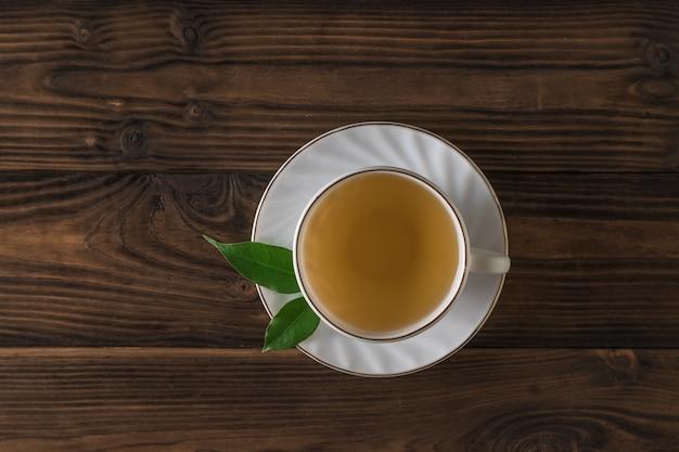Una tazza di tè fresco, un piattino e due foglie su un tavolo di legno. una bevanda tonificante utile per la salute.
