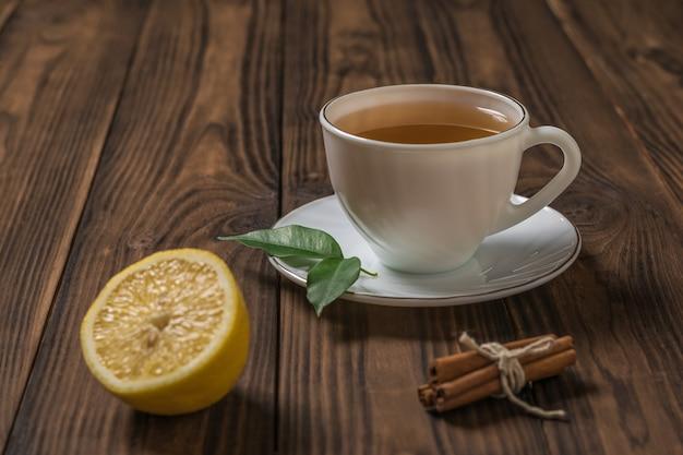 Una tazza di tè fresco con mezzo limone e bastoncini di cannella su un tavolo di legno. una bevanda tonificante utile per la salute.