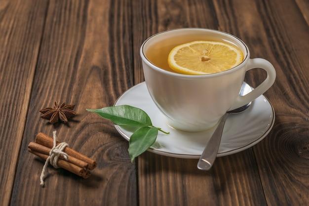 Una tazza di tè fresco con limone e cannella su un tavolo di legno al sole. una bevanda tonificante utile per la salute.