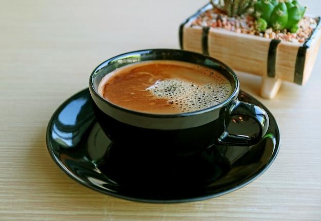 Tazza di caffè caldo schiumoso con pianta in vaso sfocata sulla tavola di legno