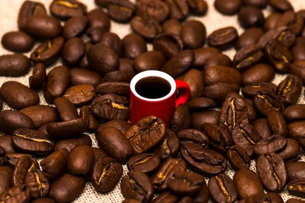 Tazza piena di chicchi di caffè sul sacco di stoffa