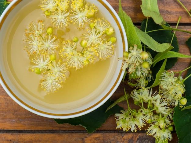 Tazza di tè verde e tiglio su fondo di legno, concetto di medicina popolare dei fiori di tiglio utile useful