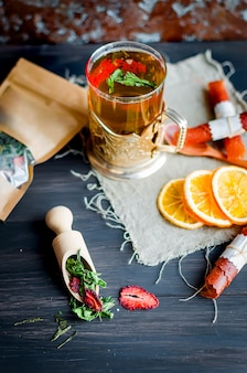 Tazza di tè verde con menta, fetta di limone, rotolo di frutta secca e foglie di menta con fragola in un cucchiaio di legno su sfondo di legno, spazio di copia