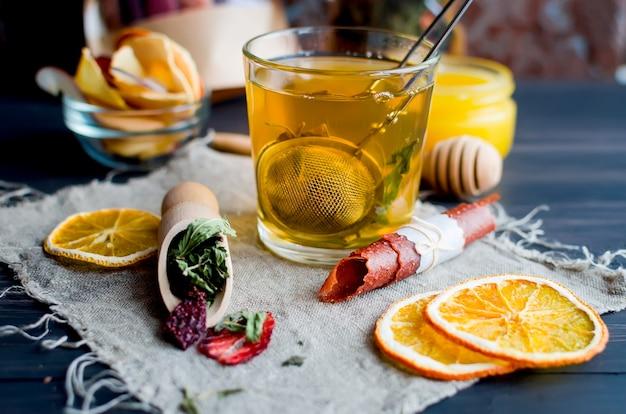 Tazza di tè verde con menta, fetta di limone, rotolo di frutta secca e foglie di menta