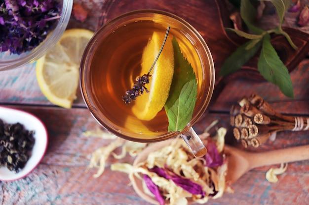 Una tazza di tè verde con fiori di erbe utili e petali secchi di limone di piante utili